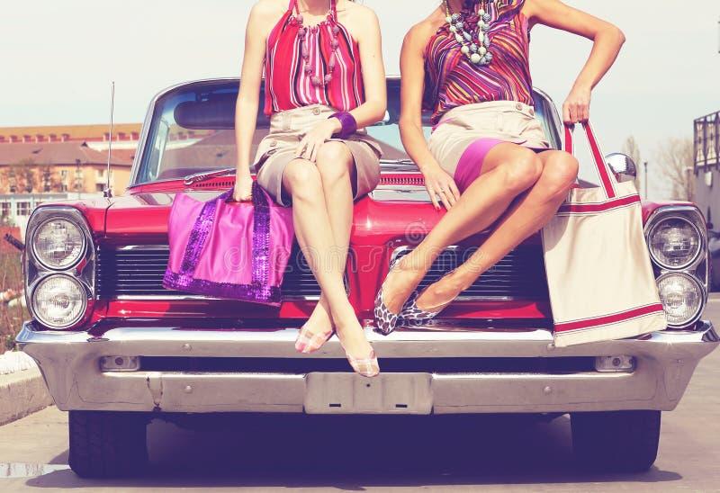 Belle gambe delle signore che posano in una retro automobile d'annata immagini stock