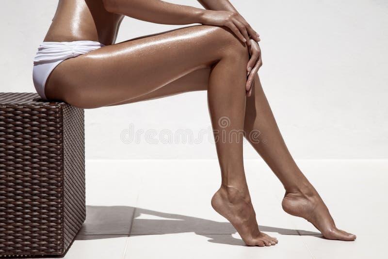Belle gambe di abbronzatura della donna. Contro la parete bianca. immagine stock