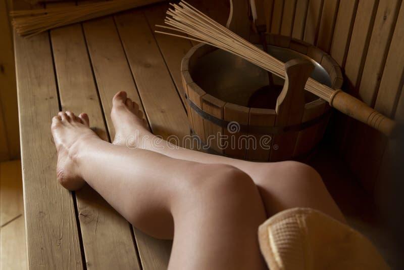 Belle gambe femminili nella sauna, accessori del bagno fotografia stock libera da diritti