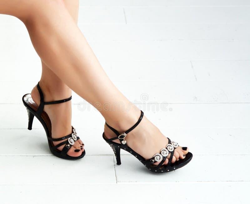 Belle gambe femminili snelle in talloni su un fondo bianco fotografia stock