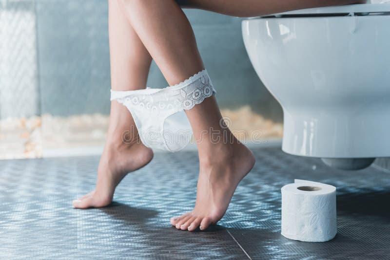 Belle gambe snelle della ragazza bianca sulla toilette immagini stock libere da diritti