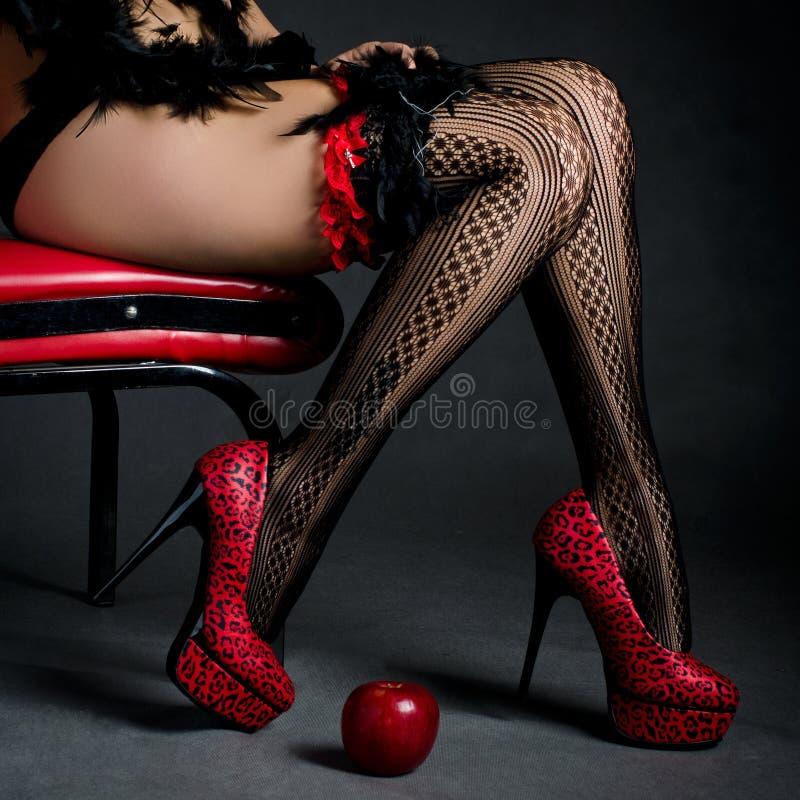 Belle gambe in tacchi alti rossi con una mela rossa immagini stock libere da diritti