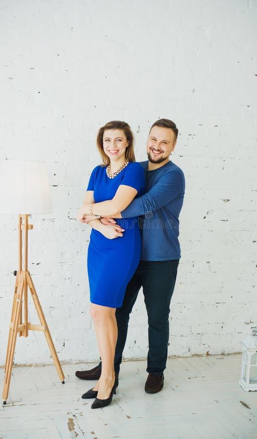 Belle giovani coppie alla moda a casa che abbracciano e che ridono della macchina fotografica Struttura verticale Vestito blu fotografia stock libera da diritti