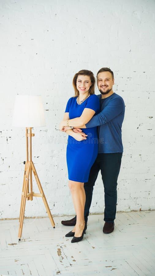 Belle giovani coppie alla moda a casa che abbracciano e che ridono della macchina fotografica Struttura verticale Vestito blu immagini stock libere da diritti