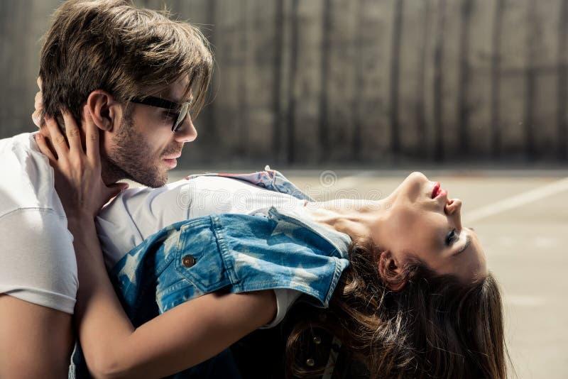 Belle giovani coppie alla moda nell'abbracciare di amore fotografia stock