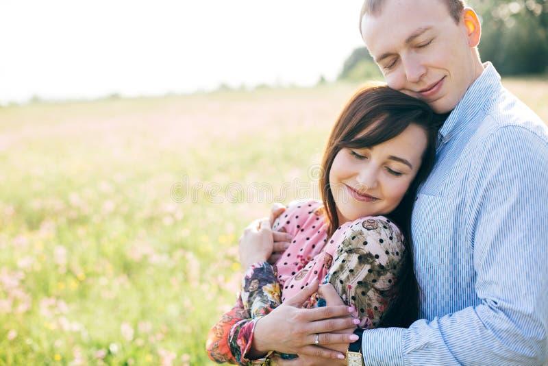 Belle giovani coppie che abbracciano delicatamente in sole nel prato di primavera Famiglia alla moda felice che abbraccia nel cam fotografia stock