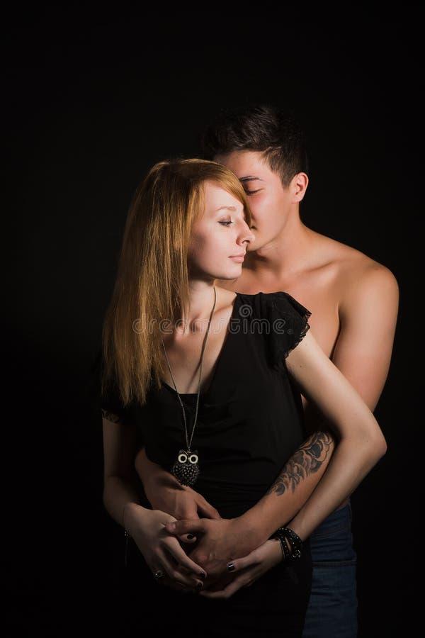 Belle giovani coppie che abbracciano e che baciano isolate su fondo nero immagine stock