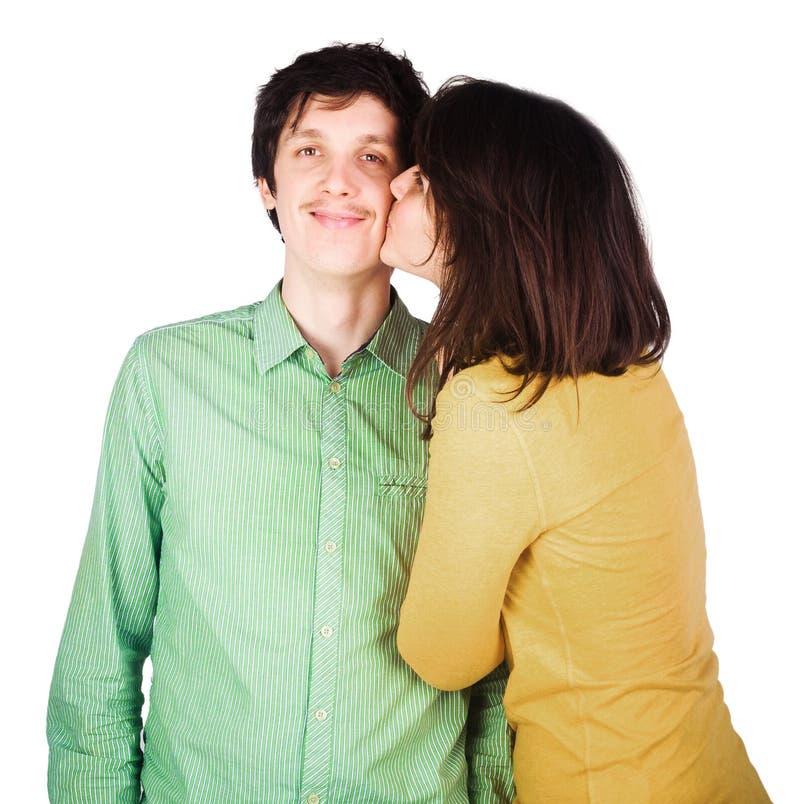 Belle giovani coppie che baciano contro il bianco immagini stock