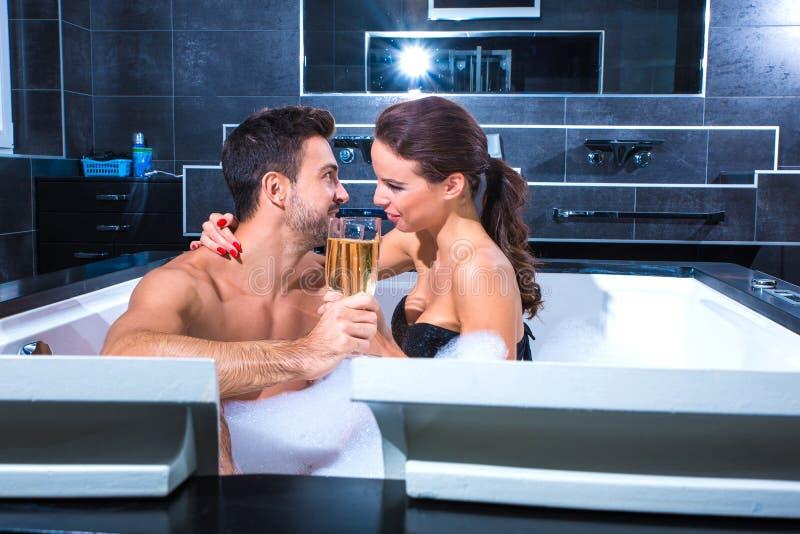 Belle giovani coppie che bevono Champagne nel mulinello immagine stock