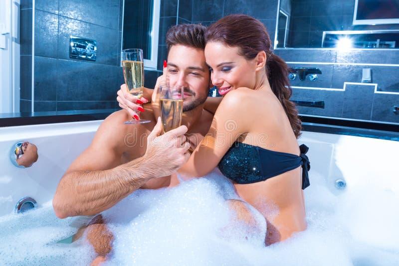 Belle giovani coppie che bevono Champagne nel mulinello immagini stock