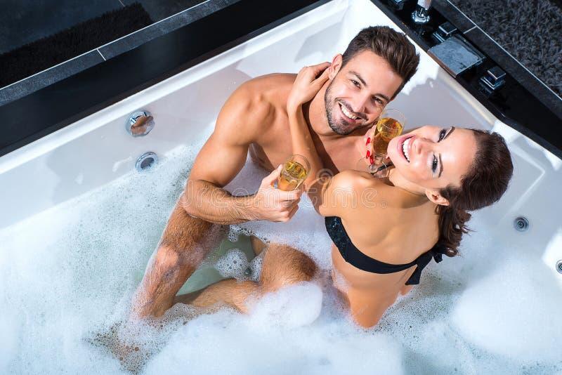 Belle giovani coppie che bevono Champagne nel mulinello fotografie stock libere da diritti