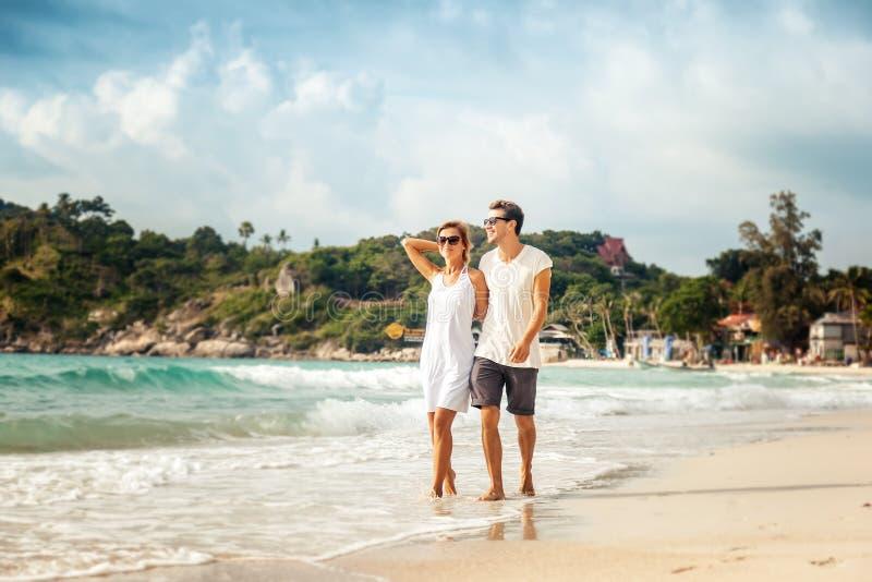 Belle giovani coppie che camminano sulla riva del mare tropicale fotografia stock