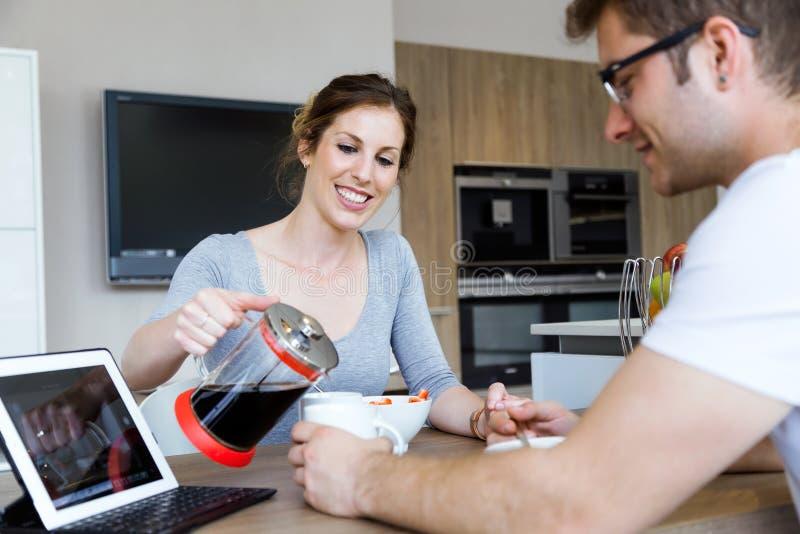 Belle giovani coppie che godono della prima colazione nella cucina a casa fotografia stock