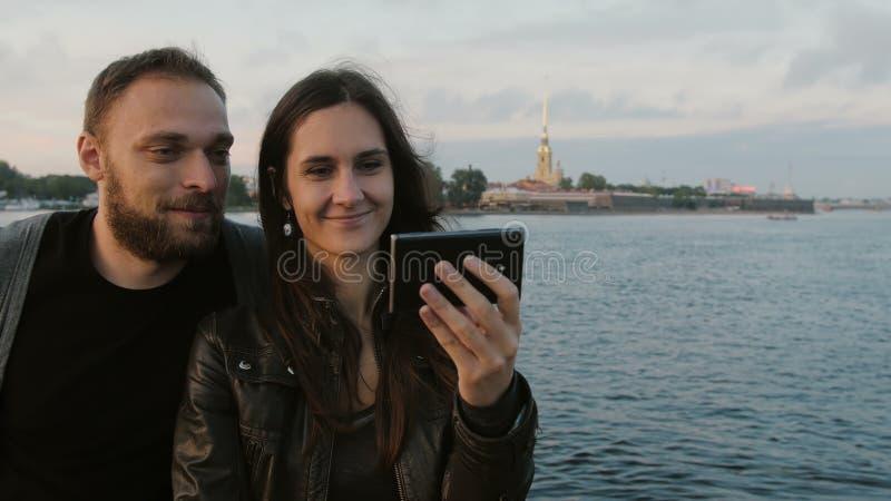 Belle giovani coppie che prendono selfie sui precedenti del fiume e della città St Petersburg 4K immagine stock libera da diritti