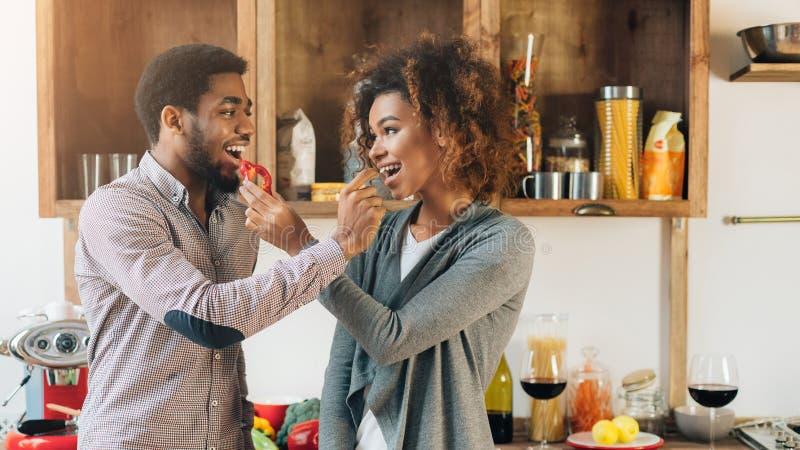 Belle giovani coppie che si alimentano in cucina fotografie stock libere da diritti