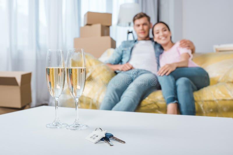 belle giovani coppie che si rilassano sullo strato mentre entrando nella nuova casa con i vetri e le chiavi del champagne fotografia stock libera da diritti