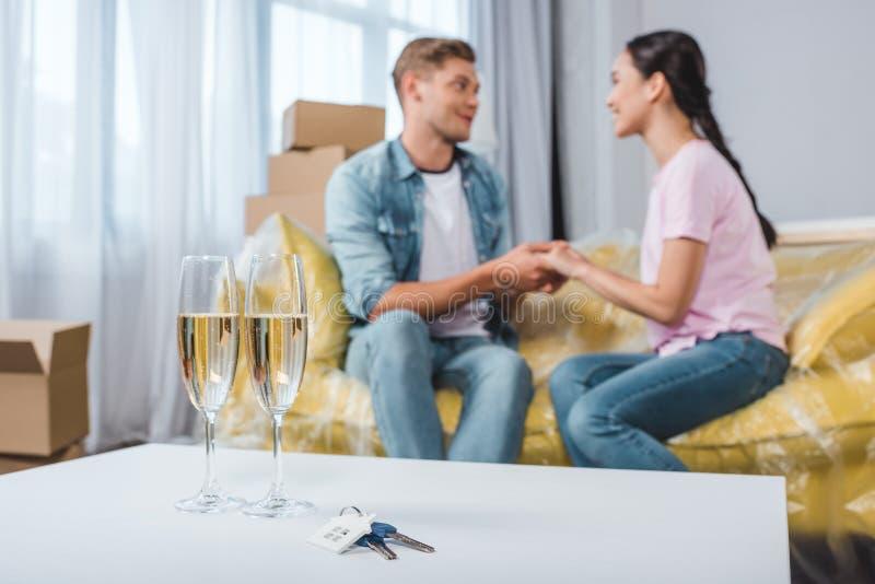 belle giovani coppie che si siedono sullo strato mentre entrando nella nuova casa con i vetri e le chiavi del champagne immagini stock libere da diritti