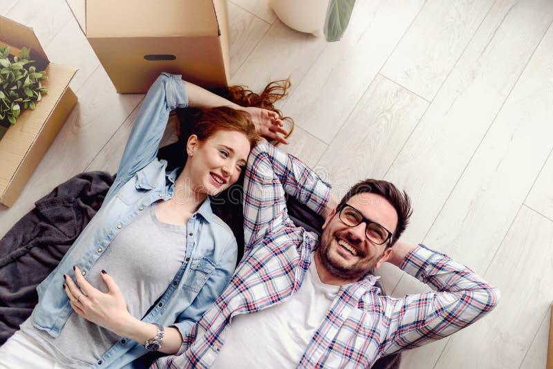 Belle giovani coppie che si trovano sul pavimento fra le scatole di cartone in loro nuovo appartamento che si sono mossi appena d fotografia stock