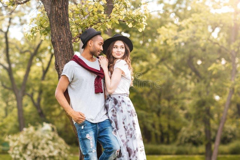 Belle giovani coppie che stanno insieme nel parco immagine stock