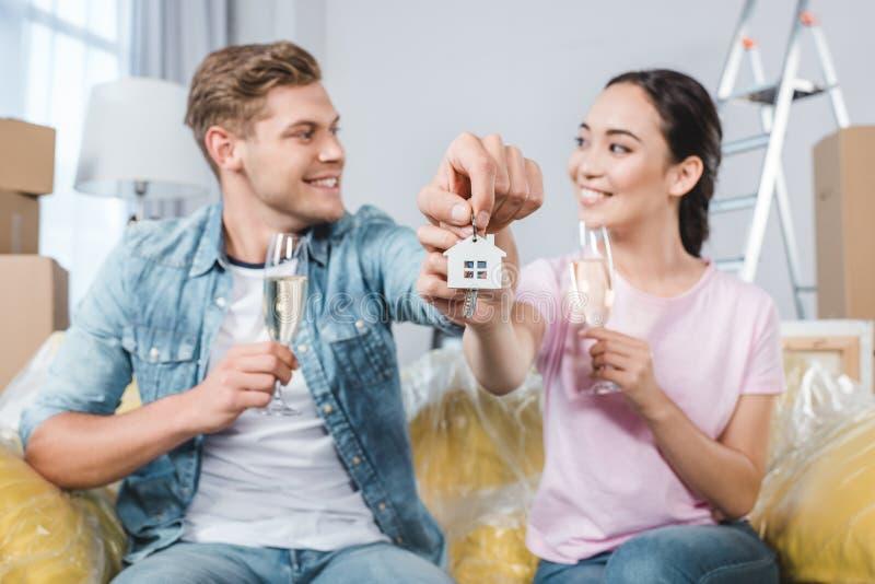 belle giovani coppie con i vetri di champagne e delle chiavi che si siedono sullo strato dopo la rilocazione in fotografia stock