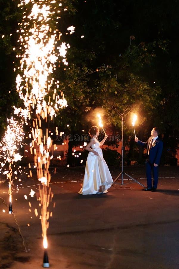 Belle giovani coppie della persona appena sposata con le torce del fuoco in loro mani e fuochi d'artificio 1 fotografia stock