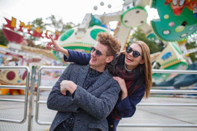 Belle giovani coppie divertendosi e ridendo nel parco di divertimenti immagine stock libera da diritti