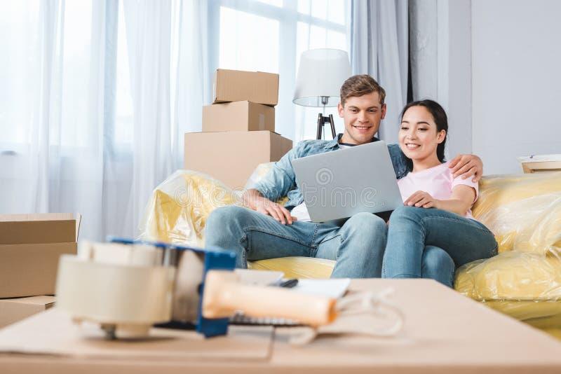 belle giovani coppie facendo uso del computer portatile sullo strato mentre entrando in immagine stock libera da diritti