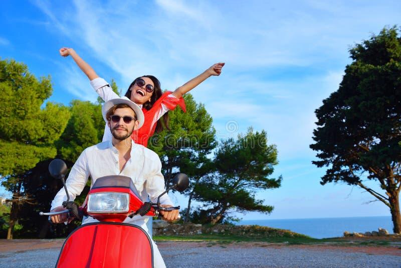 Belle giovani coppie nell'amore che gode e che si diverte della guida su un motorino fotografia stock