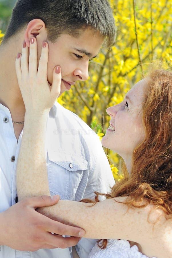 Belle giovani coppie nell'amore fra gli alberi di fioritura fotografia stock libera da diritti