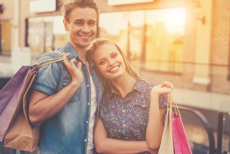 Belle giovani coppie romantiche che tengono Shopbags fotografie stock
