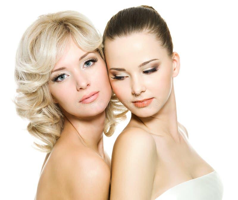 Belle giovani donne adulte sexy che propongono sul bianco immagine stock libera da diritti