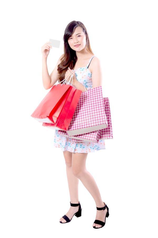 Belle giovani donne asiatiche sorridenti con le borse di vendita di acquisto isolate fotografie stock