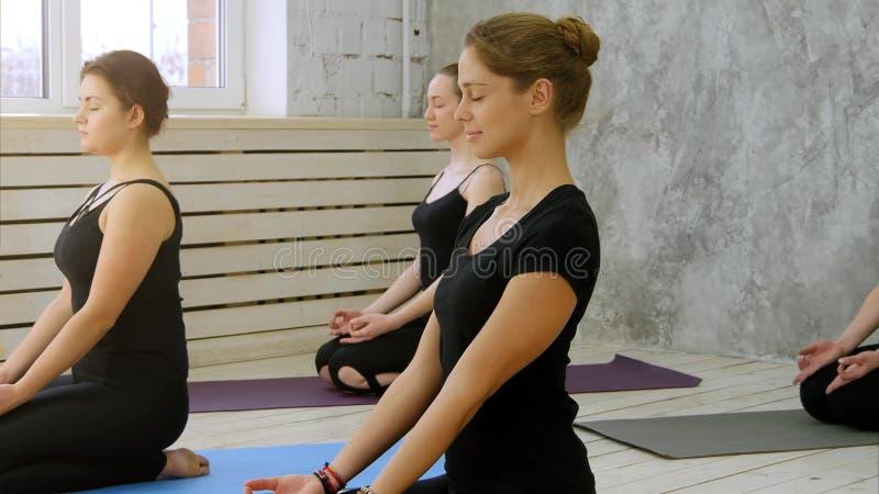 Belle giovani donne che risolvono nel sottotetto interno, facendo i exercis di yoga, meditare con il gesto di mano di mudra fotografia stock libera da diritti
