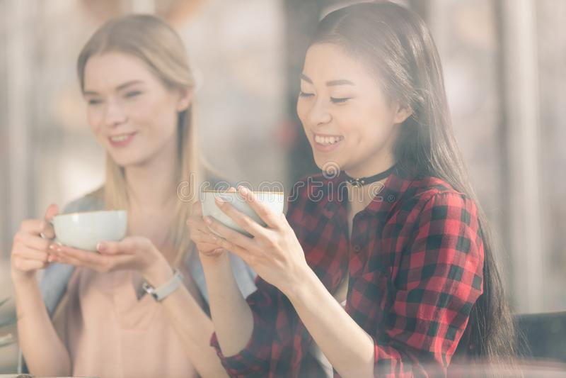 Belle giovani donne che tengono le tazze bianche e che bevono il caffè fresco del caffè immagini stock libere da diritti