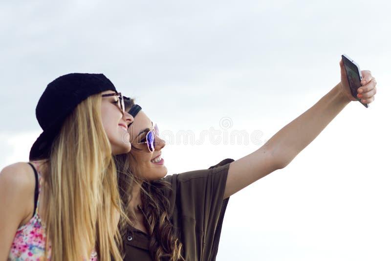 Belle giovani donne che utilizzano telefono cellulare nella via immagine stock