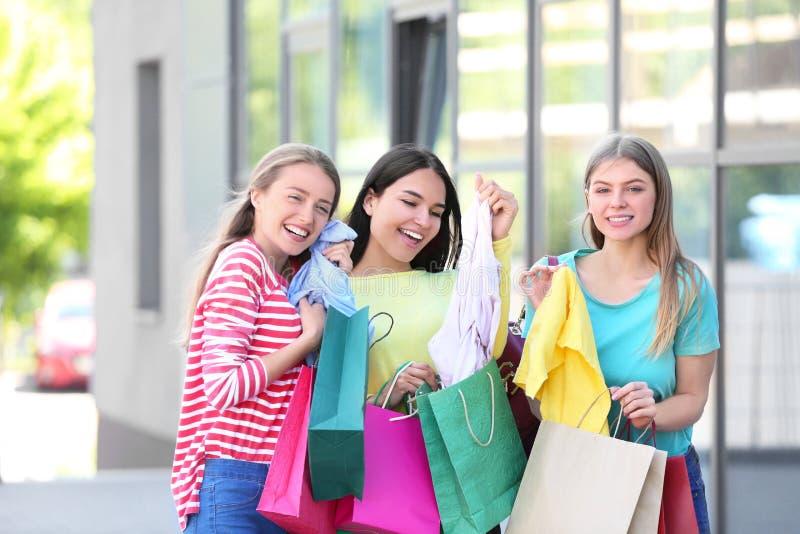 Belle giovani donne con i sacchetti della spesa ed i nuovi vestiti sulla via della città immagini stock libere da diritti
