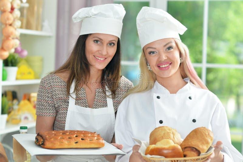 Belle giovani donne nel cuocere dei cappelli dei cuochi unici immagini stock