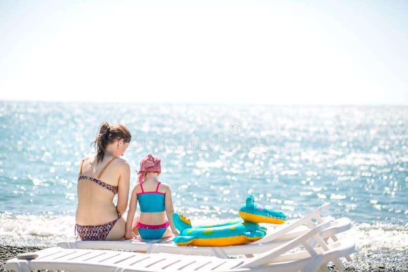 Belle giovani madre e figlia divertendosi riposo sul mare Si siedono sulla spiaggia con i ciottoli su uno sdraio, le loro parti p fotografia stock libera da diritti