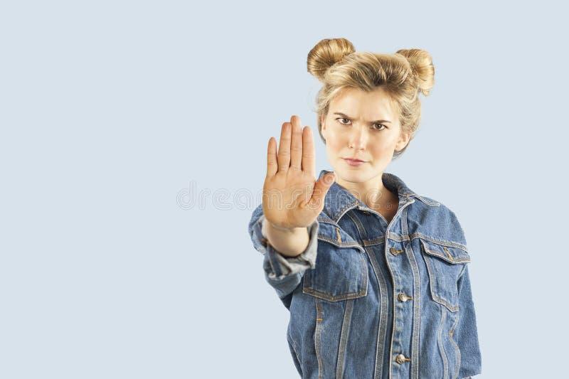 Belle giovani manifestazioni della ragazza di emrtional con le mani un fanale di arresto su un fondo isolato Fermata di opinione  immagini stock libere da diritti