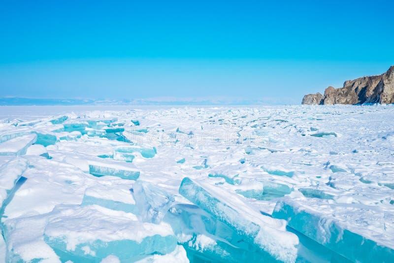 Belle glace de bleu de turquoise sur le lac Baïkal congelé avec des montagnes sur le fond image libre de droits