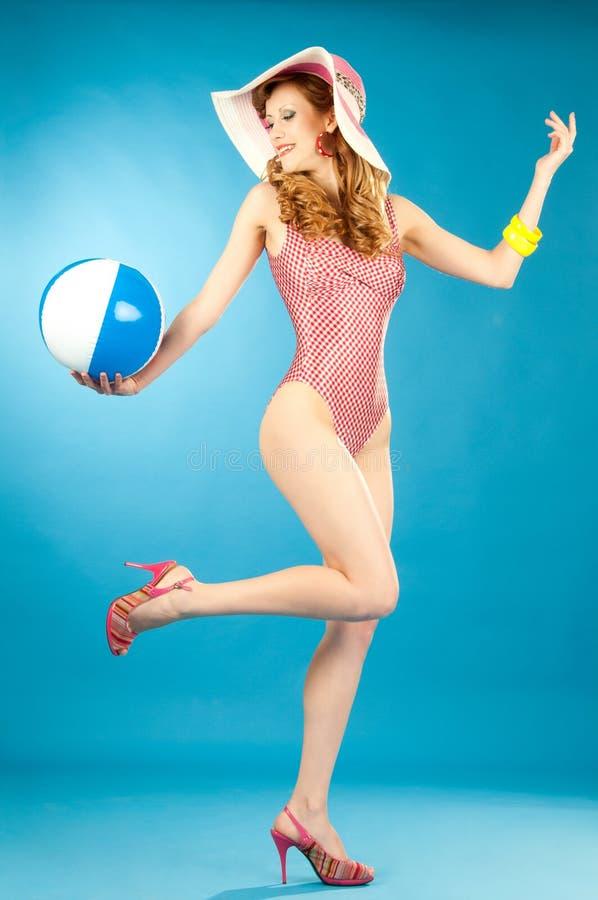 Belle goupille- riante de fille dans un bikini rose avec du ballon de plage photos libres de droits