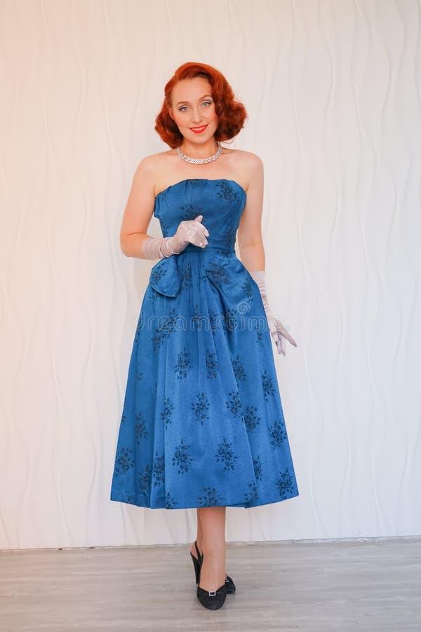 Belle goupille vers le haut de la femme se tenant dans la robe bleue contre le mur blanc dans la chambre et le sourire vides photos libres de droits