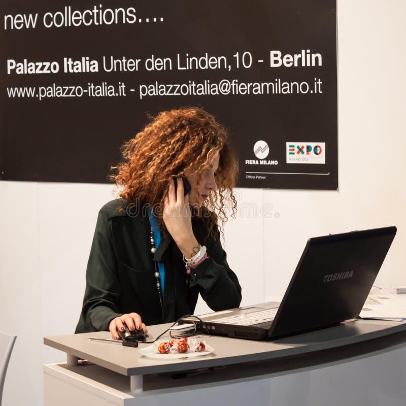Belle hôtesse travaillant à l'ordinateur au peu 2014, échange international de tourisme à Milan, Italie photographie stock