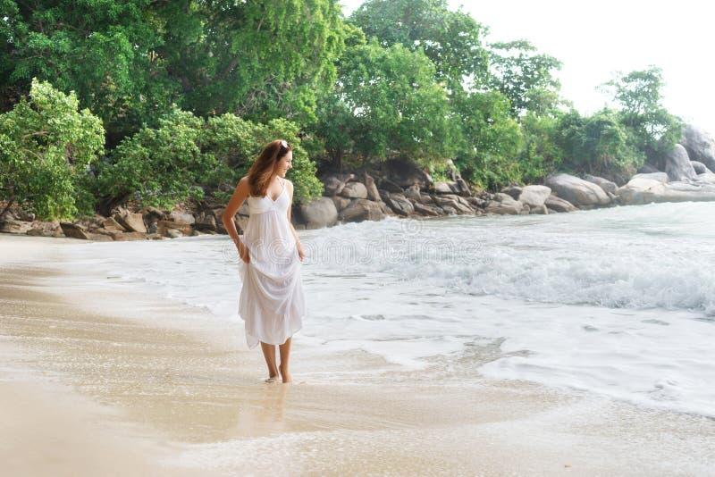 Belle, heureuse fille marchant sur le littoral photographie stock libre de droits