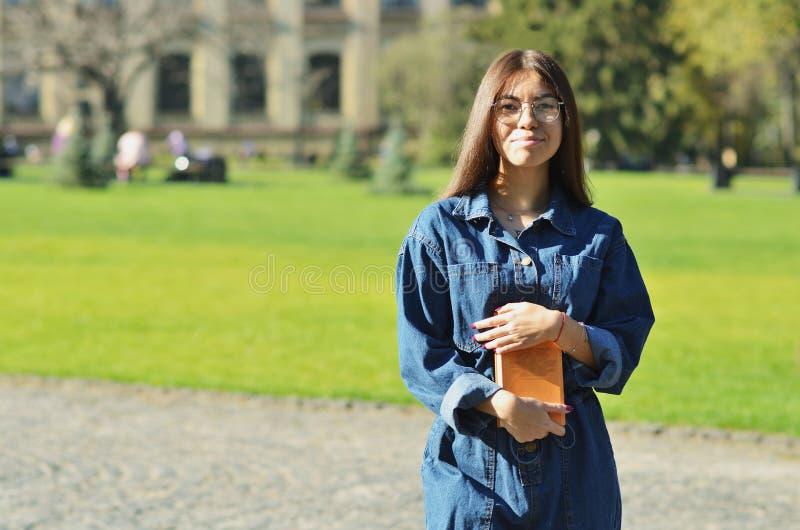 Belle, heureuse jeune position d'étudiant avec un livre en verres sur le fond image libre de droits
