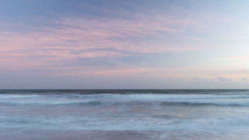 Belle image colorée artistique de paysage des vagues brouillées au coucher du soleil en Devon Enlgand images stock