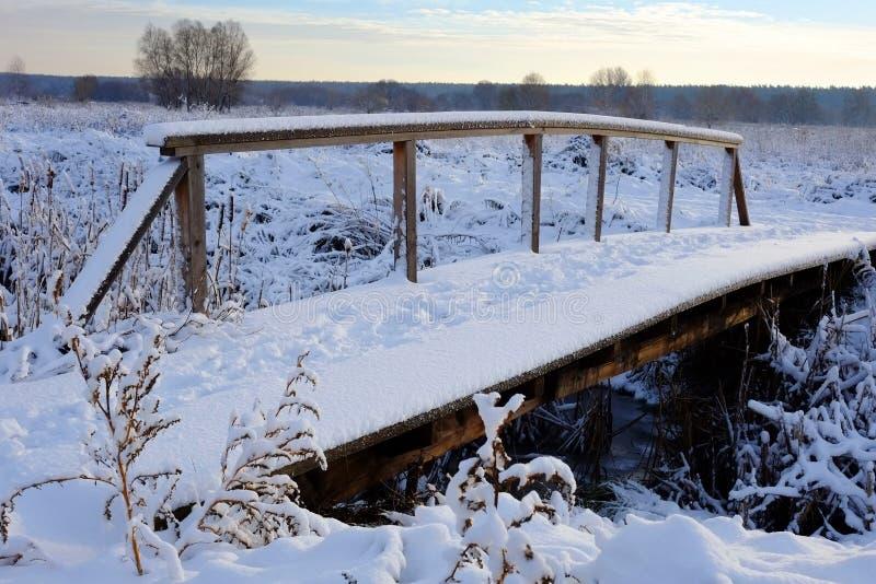 Belle image de l'hiver landscape Petit pont piétonnier en bois sous la neige photos stock