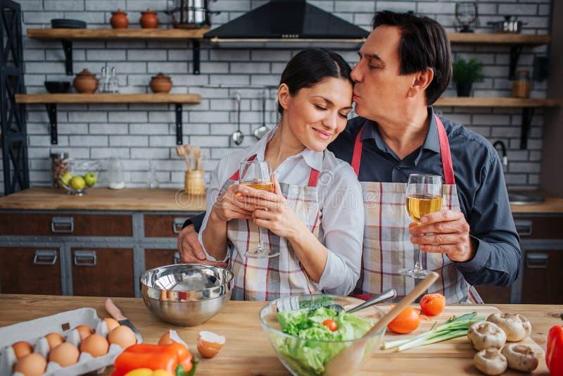 Belle image de l'homme se reposant avec la femme ensemble à la table dans la cuisine Il embrassent son front et tiennent le verre photo stock