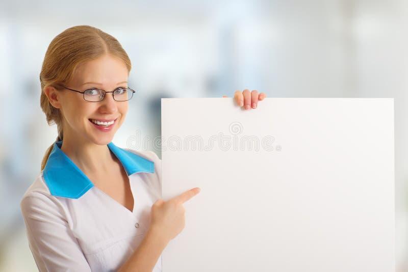 Belle infirmière retenant un panneau-réclame blanc photos stock