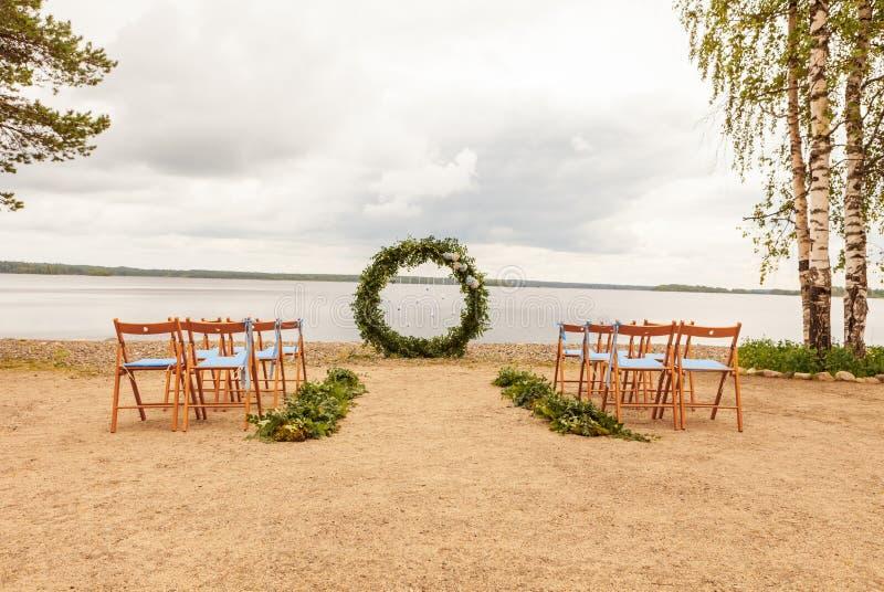 Belle installation de mariage Secteur de la cérémonie l'épousant Voûte ronde, chaises brunes décorées des fleurs, verdure Mignon, photo libre de droits